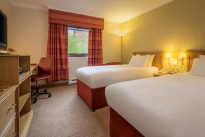 A bed or beds in a room at Hilton Warwick / Stratford-upon-Avon