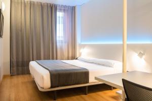 A bed or beds in a room at Vértice Roomspace