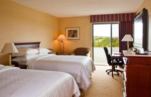 A bed or beds in a room at Radisson Hotel Hauppauge-Long Island