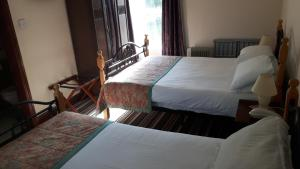 A bed or beds in a room at The Pilgrims Rest Hotel (Adults Only)