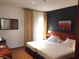 A bed or beds in a room at TRH Ciudad de Baeza