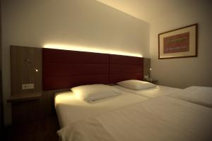 A bed or beds in a room at Airport Hotel Walldorf / Inh. Cetrico GmbH