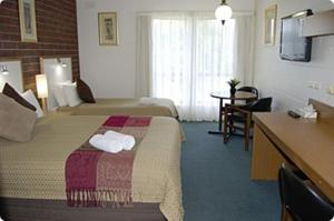 A bed or beds in a room at City Gardens Motel