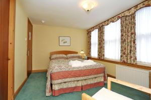 A bed or beds in a room at Butlers Guest House
