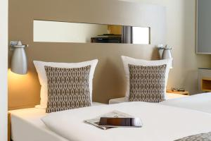 A bed or beds in a room at Mercure Hotel Düsseldorf City Nord