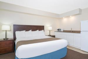 A bed or beds in a room at Days Inn & Suites by Wyndham Baxter Brainerd Area