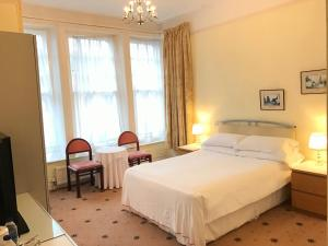 A bed or beds in a room at Churchills Hotel