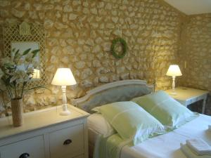 A bed or beds in a room at Les Jolies Arches, Manoir de Longeveau
