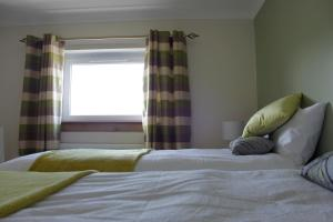 A bed or beds in a room at Caledonian House