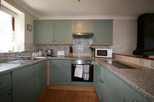 A kitchen or kitchenette at Juliots Well Cottages