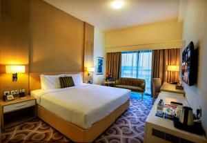 A bed or beds in a room at Metropolitan Hotel Dubai