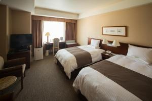 A bed or beds in a room at Rembrandt Hotel Ebina