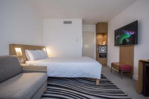 A bed or beds in a room at Novotel Bourges