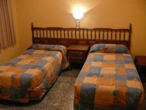 A bed or beds in a room at Hostal Rodes