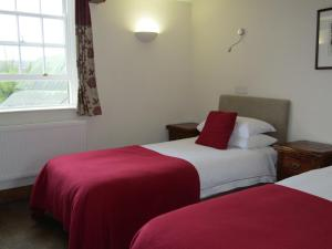 A bed or beds in a room at The Kilcot Inn
