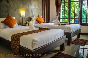 A bed or beds in a room at Thanawong Pool Villa