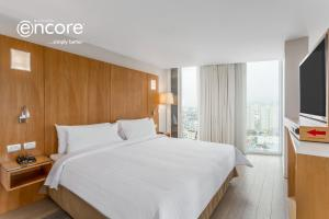 A bed or beds in a room at Ramada Encore by Wyndham Lima San Isidro