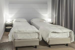 A bed or beds in a room at Tag Hotel