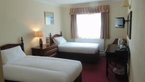 A bed or beds in a room at The Harrowgate Hill Lodge