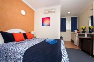 A bed or beds in a room at Tuncurry Beach Motel