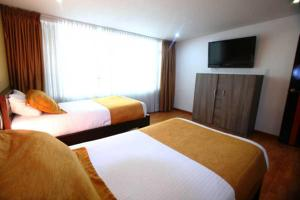 A bed or beds in a room at Hotel Expo Inn Embajada