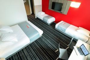 سرير أو أسرّة في غرفة في Hotel Arena Toulouse