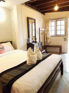 A bed or beds in a room at Niwas Ayutthaya