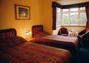 A bed or beds in a room at Nonsuch Park Hotel