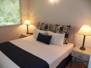 A bed or beds in a room at Palm Cove Tropic Apartments