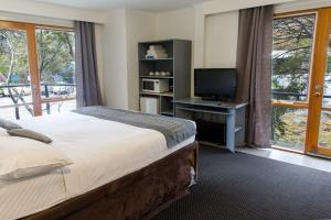 A bed or beds in a room at The River Inn Thredbo