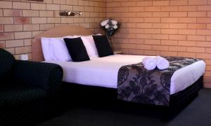 A bed or beds in a room at Roma Mid Town Motor Inn