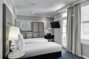 A bed or beds in a room at Hotel Kurrajong Canberra