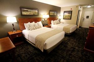 A bed or beds in a room at C'mon Inn Grand Forks