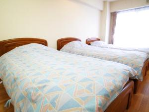 A bed or beds in a room at FLEXSTAY INN Tamagawa