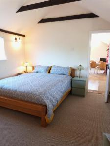 A bed or beds in a room at Copton Thatch Lodge