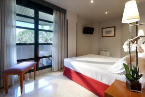A bed or beds in a room at Exe Gran Hotel Almenar