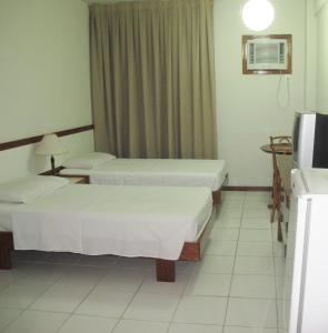 A bed or beds in a room at Hotel Aruan