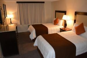 A bed or beds in a room at Longhorn Boulder Highway