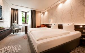 A bed or beds in a room at Land & Golf Hotel Stromberg
