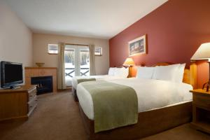 A bed or beds in a room at Coast Sundance Lodge
