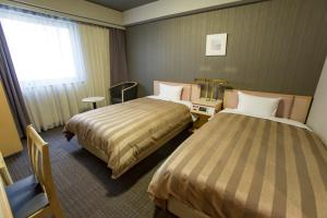 A bed or beds in a room at Hotel Route-Inn Tokyo Ikebukuro