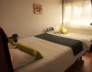A bed or beds in a room at Hôtel Belleville, Villefranche-sur-Saône Nord (Ex Inter-Hotel)