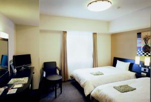 A bed or beds in a room at Hotel Route-Inn Ashikaga-2