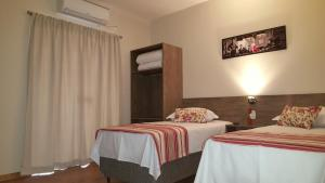 A bed or beds in a room at Hotel Recanto