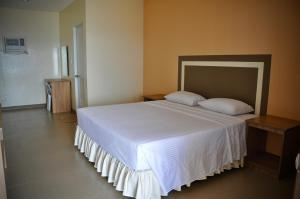 A bed or beds in a room at Matutinao Beach
