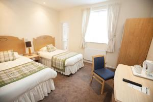A bed or beds in a room at Sandy Lodge Hotel