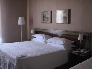 A bed or beds in a room at Hotel Aquila Bianca