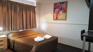 A bed or beds in a room at The Commercial Hotel Motel