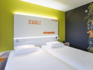 A bed or beds in a room at ibis Styles Deauville Centre