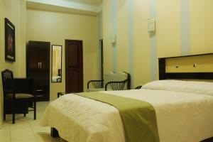 A bed or beds in a room at Atlantic Suites Hotel